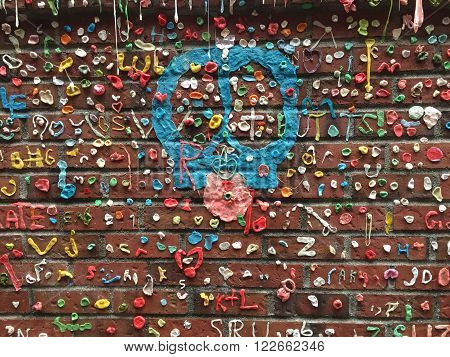 SEATTLE, WASHINGTON - March 23, 2016. A peace sign made with blue gum at the famous gum wall under Pike's Place Marketplace in Seattle, Washington. Tourists come by this alley daily to add to the gum wall or take pictures of it.