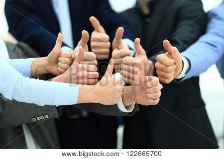 Close-up of business team holding their thumbs up