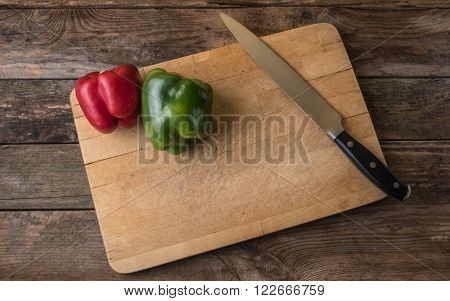 red and green bell paprica with knife and cutting board on a wooden tableâ?¨
