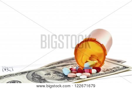 Bottle of prescription medications laying on top of a one hundred dollar bill and a prescription form isolated on white