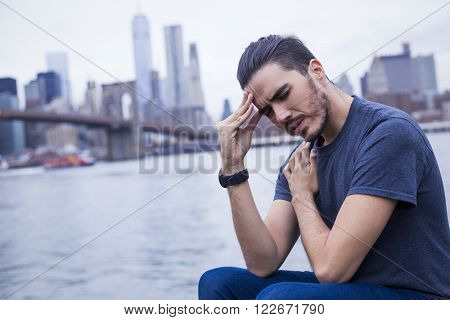 Young man suffering headache with New York city in the background