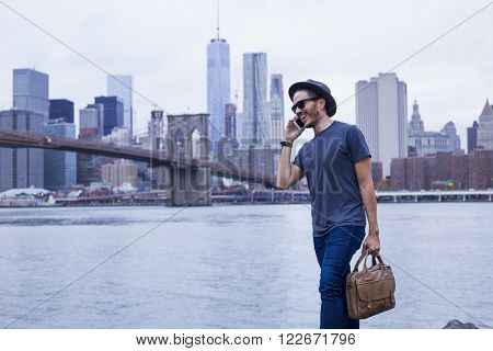 Young entrepreneur making a phone call and carrying a briefcase in New York
