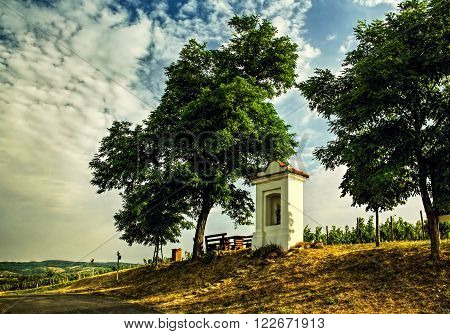 The chapel of St. Anthony on the mound near N?m?i?ky with trees a vineyard and the sky.