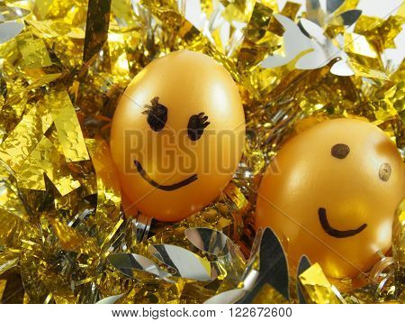 Couple of easter eggs with drawing smiling face on golden tuft, happy easter festival