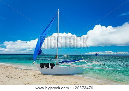 Boat docked on sand beach, Boracay island, Philippines.