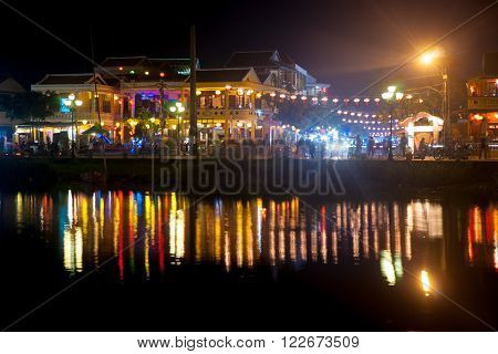 Night view of Hoi An town with light illumination and reflection in the river, Vietnam. Hoi An is the World's Cultural heritage site, famous for mixed cultures and architecture.