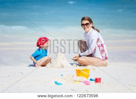 Mother and little son building a sand castle on the beach