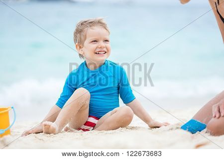 Cute little boy playing with mother on the beach on a sunny day