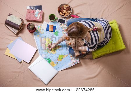 Young woman making marks on the map while sitting on the floor, view from above. Trip planning concept.