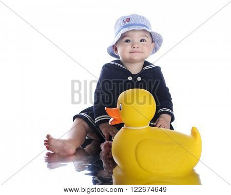 An adorable baby sailor girl sitting with her giant rubber ducky