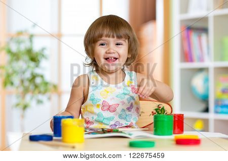 pretty child girl painting with colours in daycare or playschool