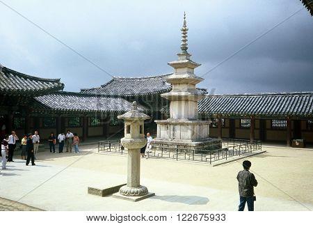 GYEONGJU CITY, NORTH GYEONGSANG PROVINCE / KOREA - CIRCA 1987:  Visitors marvel at the Seokgatap (Sakyamuni) stone pagoda, and a stone lantern, in the Bulguksa Buddhist temple.
