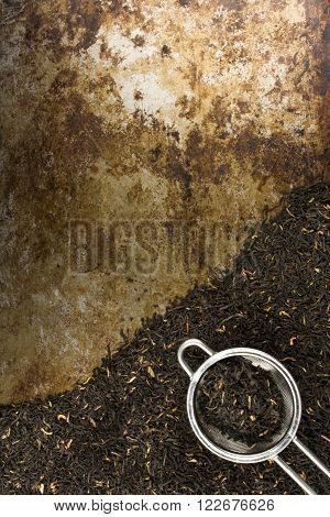 Black tea leaves and tea strainer against a rustic background with room for text