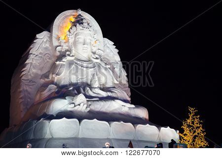 Harbin,China 01/20/2016 Guanyin the goddess of fertility at night  as a snow sculpture at the ice festival on sun island