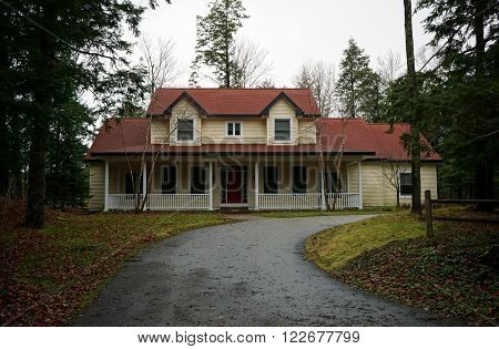 HARBOR SPRINGS, MICHIGAN / UNITED STATES - DECEMBER 23, 2015: A yellow lakefront home with a driveway along Glenn Drive in Harbor Springs.