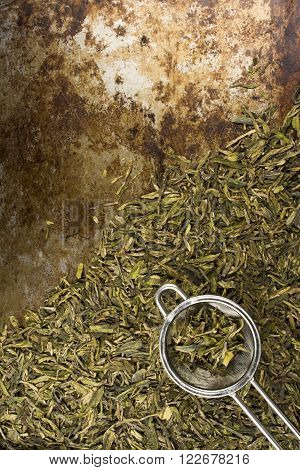 Loose leaf green tea leaves and tea strainer against a rustic backdrop with room for text