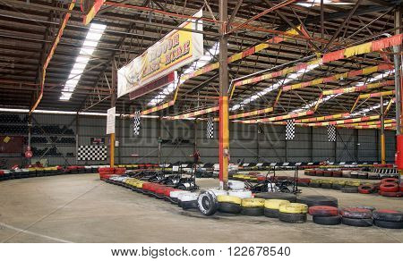 O'CONNOR,WA,AUSTRALIA-MARCH 5,2016: Indoor Kart Hire location with go karts and colourful tire boundaries and ceiling flags with people in O'Connor, Western Australia.
