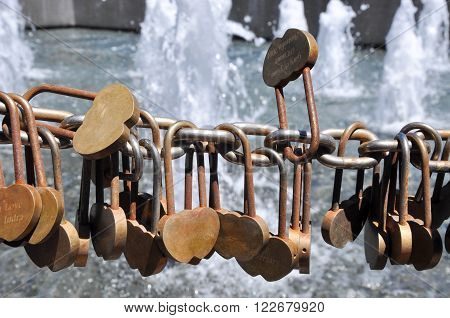 Golden love locks engraved and secured to a draped chainlink fence outside the Bell Tower in Perth, Western Australia with a water fountain in the background.