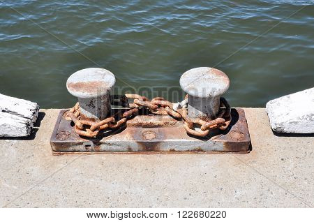 Boat mooring detail on the edge of a dock with a rusted chain wrapped in a figure eight around the two cleats.