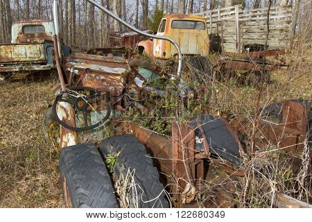 Wrecked frame of semi trailer truck in field overgrown with weeds with pickups in woods.