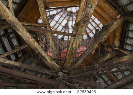 Aged and worn wooden rafters with rusting metal girders inside decaying building.