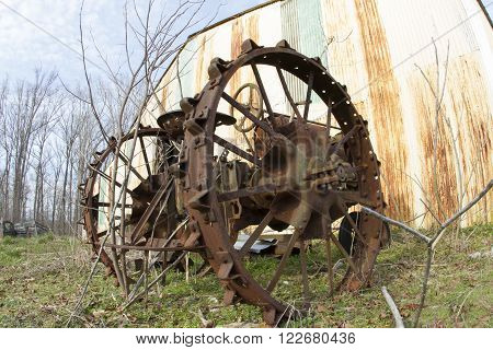 Vintage agricultural tractor outside metal shed in field.