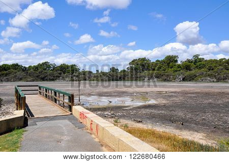 Market garden swamp with wooden pier during a drought with dried shallow landscape surrounded by green trees under a blue sky with clouds in Spearwood, Western Australia.
