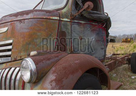 Cab of rusting semi trailer truck in farm field.