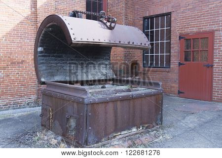 Antique metal blacksmithing tool outside old steel mill.