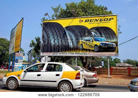 Accra Ghana - July 23 2013: There are moving cars & a taxi on the background of advertising signs and a billboard of Dunlop for West Africa tire services. Development of service market in Africa.