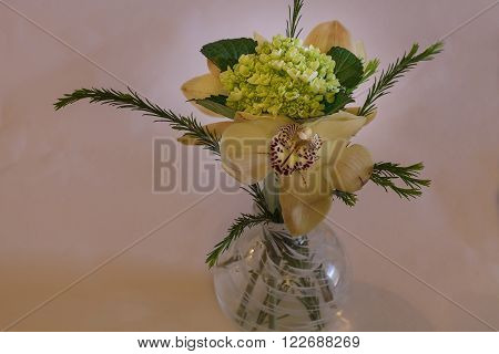 Green, white and red Cymbidium orchid arrangement in a blown glass vase at a wedding.