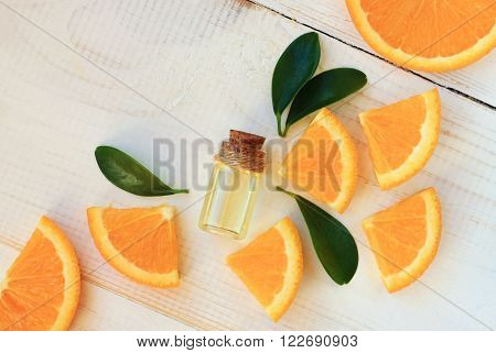 Orange aroma oil. Bottle with essential oil, citrus scattered on wooden table.