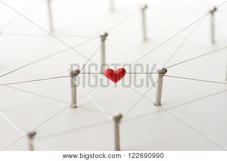 Linking entities. Network, networking, social media, internet communication abstract. Online love or matching. Web of silver wires isolated on natural white, with one connection having a red heart.