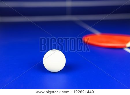 White Table Tennis Ball and a Red Racket on a Blue Table with White Net