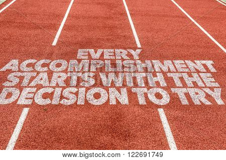 Every Accomplishment Starts With the Decision to Try written on running track