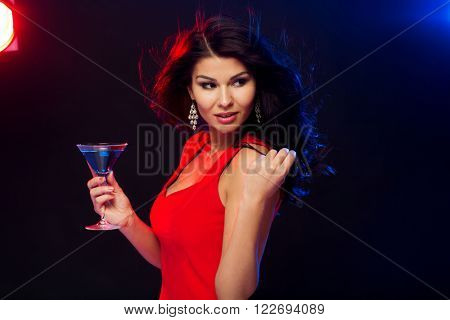 people, holidays, party, alcohol and leisure concept - beautiful sexy woman in red dress with cocktail glass dancing at night club
