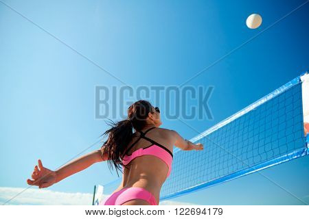 summer vacation, sport and people concept - young woman with ball playing volleyball on beach