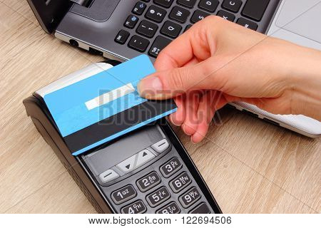 Hand of woman paying with contactless credit card with NFC technology credit card reader payment terminal and laptop finance and banking concept