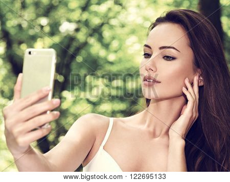 beautiful young woman selfie in the park with a ?ell phone