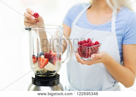 healthy eating, cooking, vegetarian food, diet and people concept - close up of woman with blender making fruit shake at home
