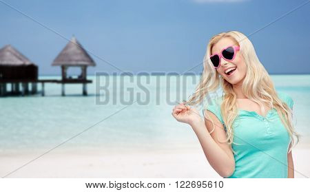 travel, tourism, summer vacation and people concept - smiling young woman or teenage girl in sunglasses holding her strand of hair over tropical beach with bungalow background
