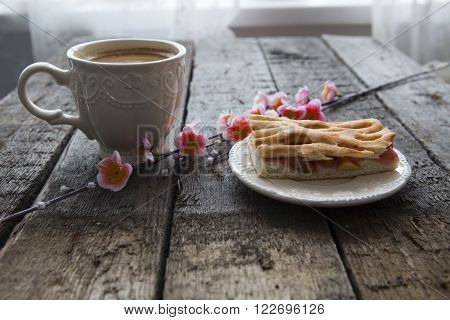 Cup of coffee with pie and pink cherry blossoms on wooden table. Sakura