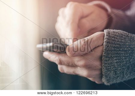 Casual man texting message on smartphone morning sunlight through window male hands using mobile phone device selective focus with shallow depth of field. ** Note: Shallow depth of field