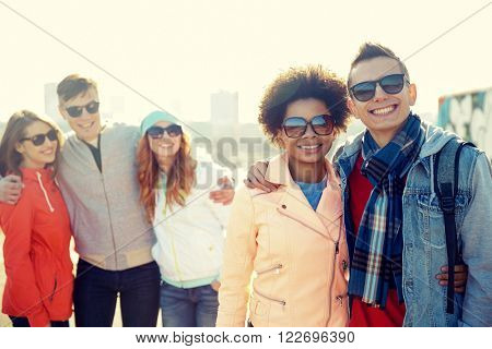 tourism, travel, people, leisure and teenage concept - group of happy friends in sunglasses hugging on city street