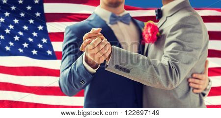 people, homosexuality, same-sex marriage and love concept - close up of happy male gay couple holding hands and dancing on wedding over american flag background