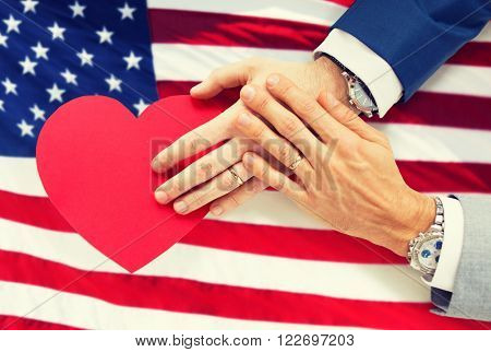 people, homosexuality, same-sex marriage, valentines day and love concept - close up of happy married male gay couple hands with red paper heart shape over american flag background