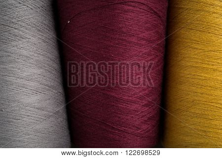Close Up Of Grey, Maroon, And Yellow Sewing Thread