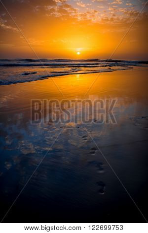 Beach with glossy surface reflecting beautiful seascape on the sunset in Maspalomas on Gran Canaria island