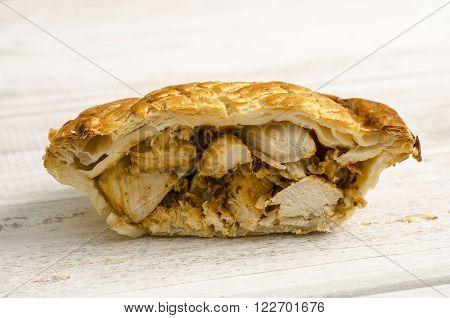 Half A Chicken Pie On A White Wooden Background