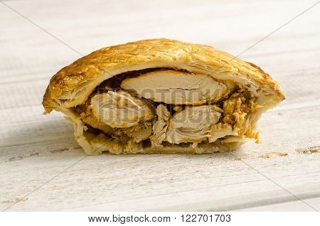 Half A Chunky Chicken Pie On White Wooden Background